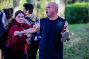 An angry father screams at police officers after the mass shooting at Marjory Stoneman Douglas High School in Parkland, Florida, on Feb 14, 2018.