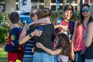 Students being comforted by parents and family after a shooting at Marjory Stoneman Douglas High School in Parkland, Florida on Feb 14, 2018.