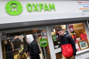 Pedestrians pass an Oxfam store in London, Britain, Feb 14, 2018.