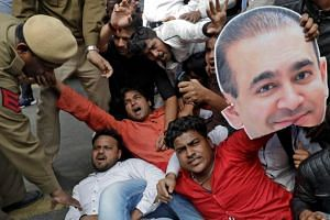 An activist of the youth wing of India's main opposition Congress party holds a cut-out with an image of billionaire jeweller Nirav Modi during a protest in New Delhi, India on Feb 16, 2018.