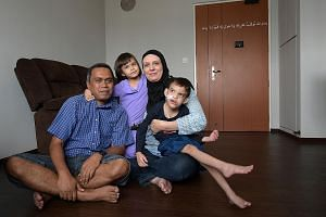 Mr Mohd Aszrin Ahmad is now a proud owner of a three-room Housing Board flat in Sembawang. He is seen here with his wife Tasha Ahrens, 42, and their children, Dean Joaquim, seven, and Sara Elizabeth, four.
