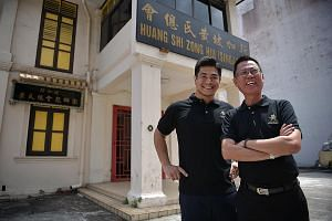Huang Clan Association's youth committee secretary-general Stanley Ng (left), 32, with association vice-president Benny Ng, 63, on its Geylang premises. Mr Stanley Ng says that in recent years, he has been talking to elder clan members about the need