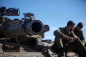 Israeli soldiers sitting on a tank during a military exercise in the Israeli-occupied Golan Height.