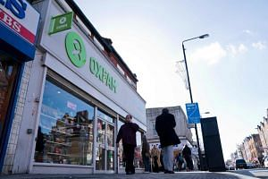People walk past a high street branch of an Oxfam charity shop in south London on Feb 17, 2018.