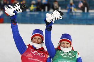 Maiken Caspersen Falla (right) and Marit Bjoergen celebrate after winning the bronze medal in the Women's Cross Country Team Sprint Free Final race, on Feb 21, 2018.
