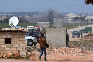 People evacuating following Turkish artillery bombardment near the Afrin crossing in northern Syria, after Syrian pro-government forces entered the region.