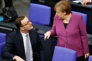 German Chancellor Angela Merkel talks to Jens Spahn during a debate at the Bundestag in Berlin on Feb 22, 2018.