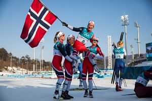 Norway's Marit Bjoergen is lifted by her compatriots after winning gold in the women's 30km cross country mass start classic at the Pyeongchang 2018 Winter Olympic Games on Feb 25, 2018.