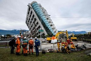 Japanese (left) and Taiwanese (right) rescue workers near the 12-storey Yun Tsui building, which was left leaning at around a 50-degree angle by the quake.
