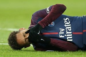 Paris Saint-Germain's Neymar lies on the pitch after sustaining an injury during the Ligue 1 match against Olympique de Marseille in Paris on Feb 25, 2018.