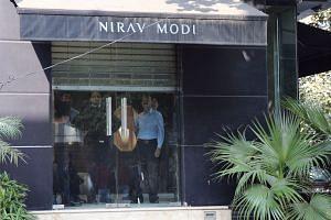 Security personnel stand near the half-closed shutter of a Nirav Modi designer's jewellery showroom in New Delhi on Feb 15, 2018.