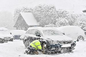 A man fitting snow chains to his car in the village of Brenchley in south-east England on Feb 27, 2018.