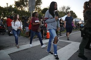 Students walking to Marjory Stoneman Douglas High School as they attend classes for the first time since the shooting.
