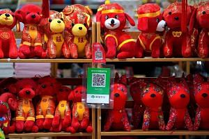 QR codes for WeChat Pay - developed by Tencent - and Alibaba payment platform Alipay at a toy shop in Beijing. The sheer size of Tencent and Alibaba and their increasingly world-spanning ambitions have made rivalry inevitable, says the writer.