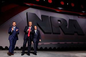 NRA Executive Director Chris Cox (left) and Executive Vice President and CEO Wayne LaPierre (right) with US President Donald Trump (centre) at an National Rifle Association forum in Atlanta on April 28, 2017.