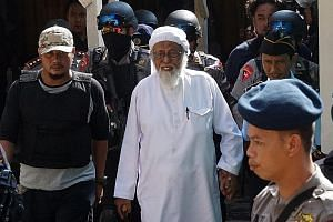Indonesian radical Muslim cleric Abu Bakar Bashir (centre) being escorted by anti-terror police as he arrived for his appeal trial in Cilacap, Central Java, in 2016. Bashir was sentenced to 15 years in jail and was at first housed in isolation in a m
