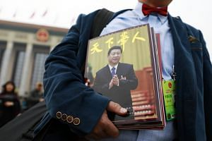 A foreign journalist carrying a magazine with Chinese President Xi Jinping on its front cover outside Beijing's Great Hall of the People.
