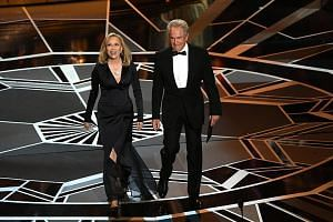 Actors Faye Dunaway (left) and Warren Beatty walk onstage during the 90th Annual Academy Awards at the Dolby Theatre in Hollywood, California on March 4, 2018.