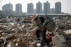 A migrant worker carrying scrap material she collected from debris of demolished buildings at the outskirts of Beijing, China, on Oct 1, 2017.