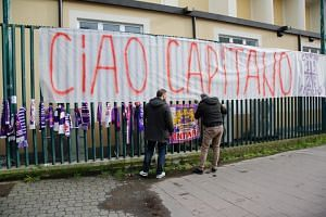 A Fiorentina supporter puts up scarves, flowers and banners in memory of the club's deceased captain Davide Astori outside the Artemio Franchi stadium in Florence on March 4, 2018.