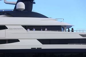 People are seen on deck after Indonesian officials boarded the luxury yacht Equanimity at Benoa Bay in Bali on Feb 28, 2018.