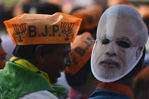 Bharatiya Janata Party (BJP) supporters celebrate with Indian Prime Minister Narendra Modi's mask after getting the absolute majority against Communist Party of India (Marxist) CPI(M) in Tripura state Assembly election in Agartala, India, on March 3,