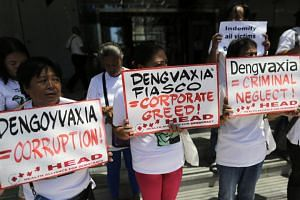Protesters stage a demonstration at the Sanofi Pasteur office against the drug company's deal with the government on the controversial anti-dengue vaccine Dengvaxia in Manila on March 5, 2018.