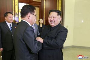 North Korean leader Kim Jong Un greets a member of the special delegation of South Korea's President at a dinner in this photo released by North Korea's KCNA, on March 6, 2018.