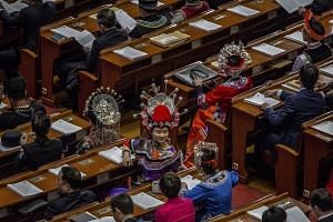 Delegates on the floor of the Great Hall of the People, some of them wearing the ethnic dress of their home districts, during the opening of the National People's Congress on March 5, 2018.