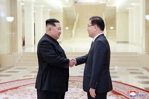 North Korean leader Kim Jong Un (left) shaking hands with South Korean chief delegator Chung Eui Yong, on March 6, 2018.