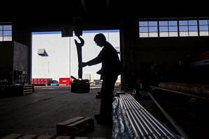 A sawyer uses a giant magnet to move a cut of machine grade steel at the Pacific Machinery & Tool Steel Company on March 6, 2018 in Portland, Oregon.