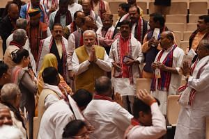 Indian Prime Minister Narendra Modi (centre) gestures as he is welcomed by his party members as he arrives for the Bharatiya Janata Party parliamentary meeting in New Delhi on March 6, 2018.