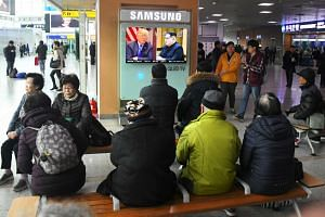 People watching a television news report showing pictures of US President Donald Trump (left) and North Korean leader Kim Jong Un at a railway station in Seoul, on March 9, 2018.
