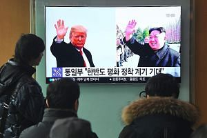 South Koreans at a railway station in Seoul watching a news report yesterday showing pictures of US President Donald Trump and North Korean leader Kim Jong Un, who are set to meet for a historic summit.