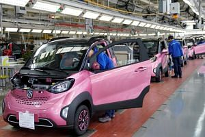 Workers inspect Baojun E100 all-electric battery cars at a final assembly plant operated by General Motors Co and its local joint-venture partners in Liuzhou, China, on Dec 27, 2017.