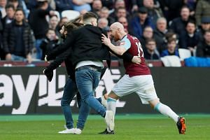 Fans clash with West Ham United's James Collins after invading the pitch.