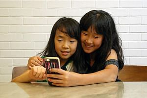 (From far left) Trina Shah, four, and her twin sisters, Tiara and Tania Shah, eight, all have mobile phones. Sisters Gayle Jiow (left), nine, and Genevieve Jiow, 12, with a mobile phone that they share. Ms Kavitha Velayutham gave her daughter Tejaswi