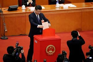 Chinese President Xi Jinping drops his ballot during a vote on constitutional amendments at the third plenary session of the National People's Congress (NPC) at the Great Hall of the People in Beijing, China, on March 11, 2018.