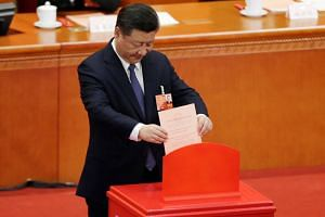 Chinese President Xi Jinping drops his ballot during a vote on a constitutional amendment lifting presidential term limits, at the third plenary session of the National People's Congress at the Great Hall of the People in Beijing on March 11, 2018.