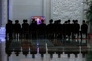Chinese security officers and staff watching a live telecast of President Xi Jinping at the fourth plenary session of the National People's Congress at the Great Hall of the People in Beijing yesterday.