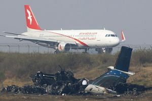 An Airarabia plane is seen on a runway next to the wreckage of US-Bangla flight BS211 at the Tribhuvan International Airport in Kathmanduu, Nepal, on March 13, 2018.