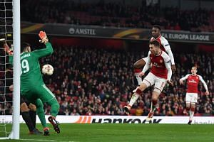 Arsenal's English striker Danny Welbeck (top, right) scores the team's third goal during the Uefa Europa League round of 16 second-leg football match between Arsenal and AC Milan, on March 15, 2018.