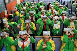 Primary school pupils wear virtual reality headsets inside a classroom in Xiangxi Tujia and Miao Autonomous Prefecture, China, on March 14, 2018.