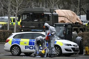 Military personnel in protective clothing removes vehicles from a car park in Salisbury, on March 11, 2018.