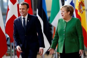 French President Emmanuel Macron and Germany's Chancellor Angela Merkel arrive at a European Union heads of state informal meeting in Brussels, Belgium, Feb 23, 2018.