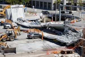 Workers removing debris from a collapsed pedestrian bridge at Florida International University, on March 16, 2018.