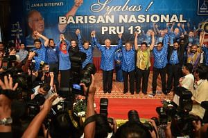 Malaysian Prime Minister Najib Razak and his fellow Barisan Nasional party members celebrate their 2013 general election win at Putra World Trade Centre in Kuala Lumpur on May 6, 2013.
