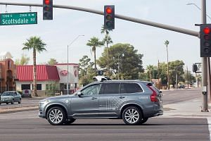 An Uber car, also a Volvo like this one (left), was in autonomous mode with an operator behind the wheel when it struck and killed a woman at this intersection (above) on Sunday in Tempe, Arizona.