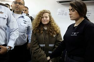 Ahed Tamimi enters a military courtroom escorted by Israeli security personnel at Ofer Prison on Jan 15, 2018.