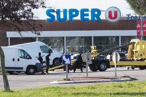 Policemen at work outside the Super U supermarket in the town of Trebes, southern France on March 23, 2018, after special forces killed a gunman who had taken several people hostages for more than three hours.
